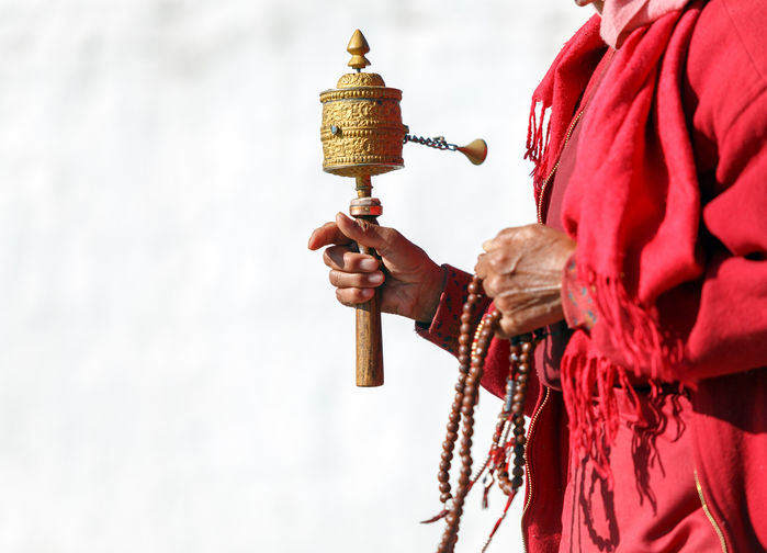 Munk i röd kaftan med bönesnurra